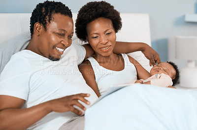 Buy stock photo Shot of a young couple using a digital tablet while their infant daughter sleeps in their bedroom at home