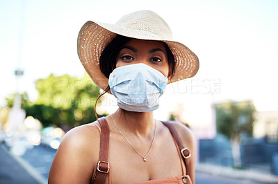 Buy stock photo Portrait of an attractive young woman wearing a surgical mask while out in the city