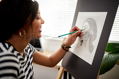 Buy stock photo Shot of an attractive young artist drawing a portrait of a woman inside her studio