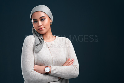 Buy stock photo Cropped shot of an attractive young woman wearing a headscarf and standing with her arms folded against a black background
