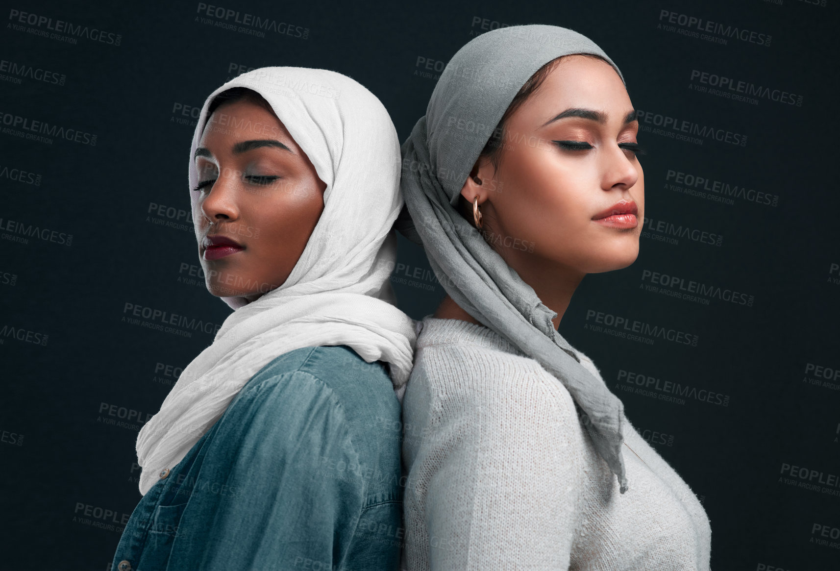 Buy stock photo Cropped shot of two attractive young women wearing hijabs and standing back to back against a black studio background