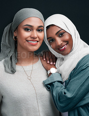 Buy stock photo Cropped shot of two attractive young women wearing hijabs and standing close together against a black background in the studio