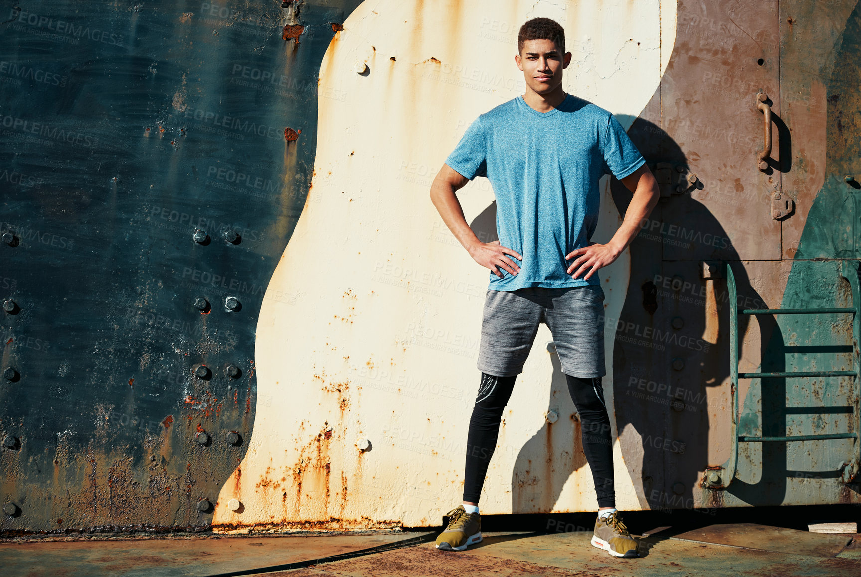 Buy stock photo Shot of a handsome young man posing with his hands on hips while out exercising