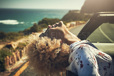 Buy stock photo Cropped hot of a young woman enjoying herself on a road trip