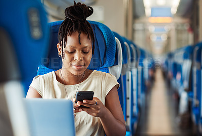 Buy stock photo Cropped shot of an attractive young woman sitting in a train and texting on her cellphone
