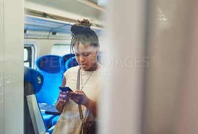Buy stock photo Cropped shot of an attractive young woman standing in a train alone and using her cellphone