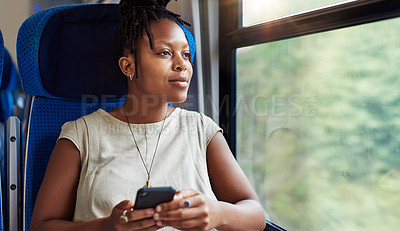 Buy stock photo Cropped shot of an attractive young woman sitting in a train alone and looking contemplative while using her cellphone