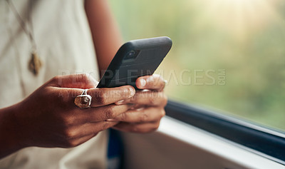 Buy stock photo Cropped shot of an unrecognizable woman sitting alone on the train and texting on her cellphone
