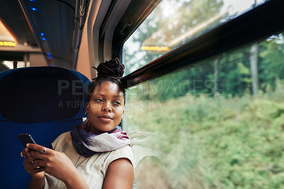 Buy stock photo Cropped shot of an attractive young woman sitting alone in a train and using her cellphone