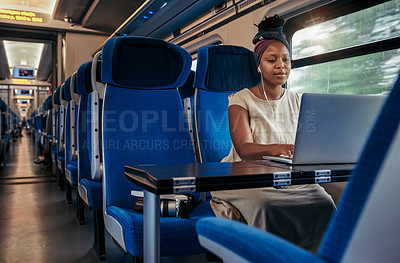 Buy stock photo Cropped shot of an attractive young woman sitting and wearing earphones while using her laptop in the train