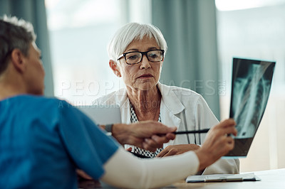 Buy stock photo Cropped shot of a confident mature doctor examining a x-ray with a nurse while being seated a desk inside of a doctor's office