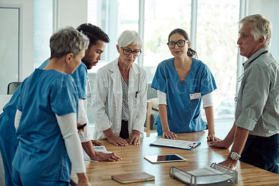 Buy stock photo Cropped shot of two confident mature doctor's having a discussion with three nurses inside of a office during the day