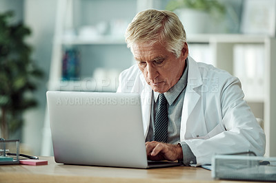 Buy stock photo Cropped shot of a mature male doctor working on a laptop while being seated at his desk inside of a doctor's office during the day
