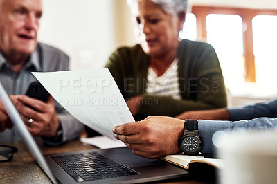 Buy stock photo Cropped shot of an unrecognizable businessman sitting with his senior clients and explaining paperwork during a meeting