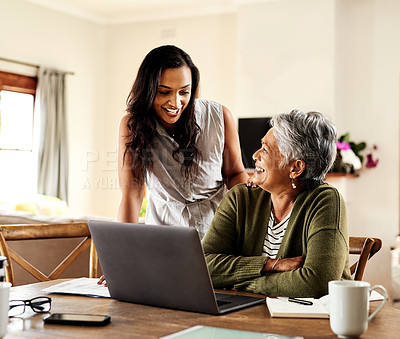 Buy stock photo Cropped shot of a young attractive woman bonding with her grandmother before helping her with her finances in their home