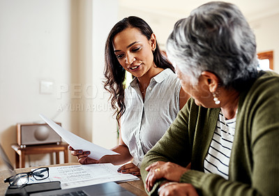 Buy stock photo Cropped shot of an attractive young woman sitting and explaining financial documents to her grandmother in their home
