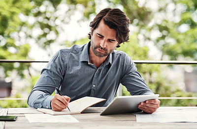 Buy stock photo Cropped shot of a handsome young businessman sitting outside alone and writing out his financial plan while using a tablet