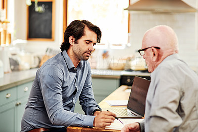 Buy stock photo Cropped shot of a handsome young financial advisor sitting with his senior client to discuss their finances in their home