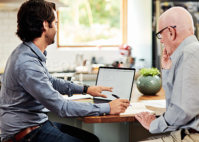 Buy stock photo Cropped shot of a young financial advisor sitting with his senior client and using a laptop during a meeting