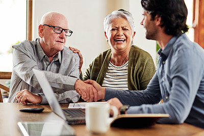 Buy stock photo Cropped shot of a senior couple sitting and shaking hands with their financial advisor after a meeting in their home