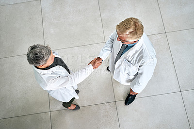Buy stock photo High angle shot of two doctors shaking hands in a hospital