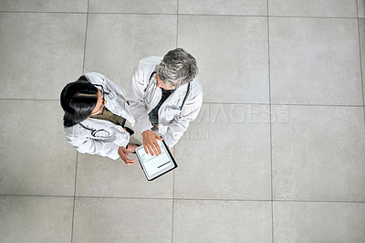 Buy stock photo High angle shot of two doctors using a digital tablet together in a hospital