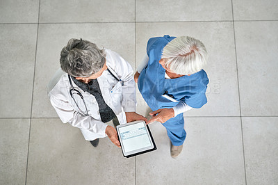 Buy stock photo High angle shot of two medical practitioners using a digital tablet together in a hospital