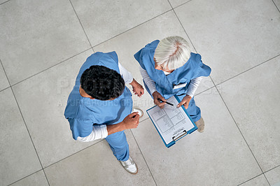 Buy stock photo High angle shot of two medical practitioners going through paperwork together in a hospital