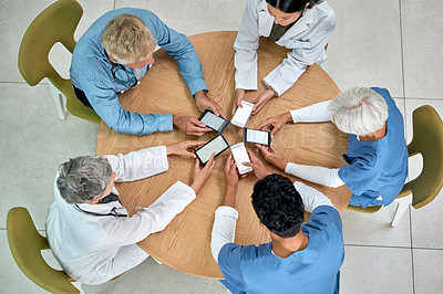 Buy stock photo High angle shot of a group of medical practitioners using their cellphones in synchronicity