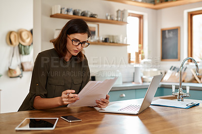 Buy stock photo Cropped shot of an attractive young woman going through paperwork while doing her budget at home