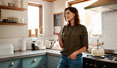 Buy stock photo Cropped shot of an attractive young woman looking thoughtful while having a cup of coffee in her kitchen at home