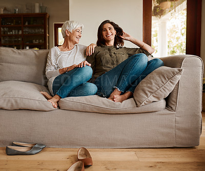 Buy stock photo Full length shot of an affectionate young woman spending time with her elderly mother in their living room at home