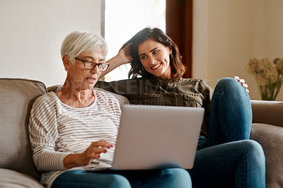 Buy stock photo Cropped shot of an affectionate young woman smiling at her elderly mother while she's using a laptop in their living room at home