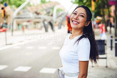 Buy stock photo Cropped portrait of an attractive young woman standing on the street and smiling while sight-seeing alone