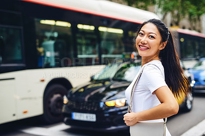 Buy stock photo Cropped portrait of an attractive young woman standing on the side of a busy road and smiling while on vacation