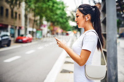 Buy stock photo Cropped shot of an attractive young woman wearing earphones and using her cellphone while standing on the street in Spain