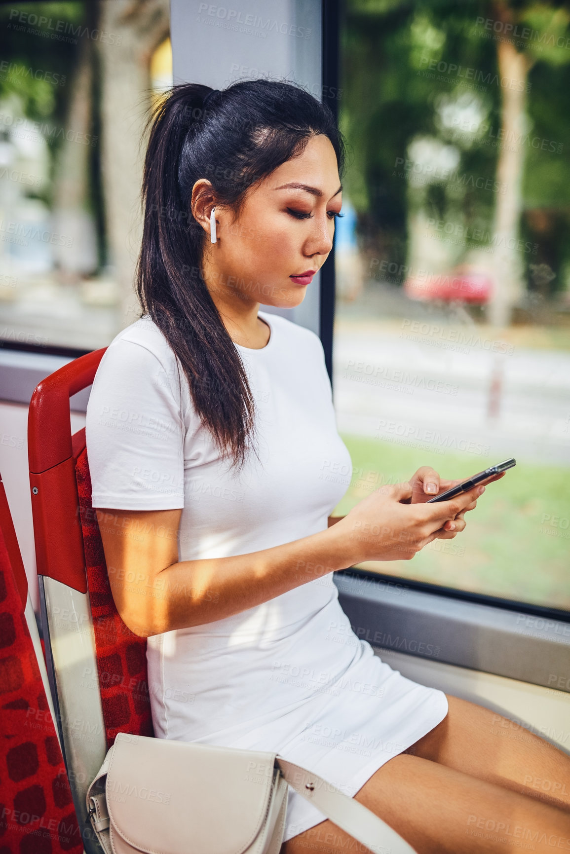 Buy stock photo Cropped shot of an attractive young woman wearing earphones and using her cellphone while sitting in a bus