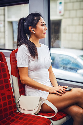 Buy stock photo Cropped shot of an attractive young woman wearing earphones and listening to music from her cellphone while in a bus