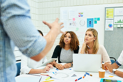 Buy stock photo Shot of two attractive young designers listening attentively during a meeting with colleagues at work