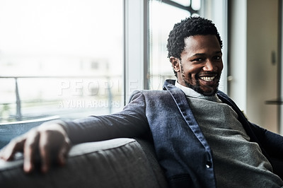 Buy stock photo Portrait of a handsome young businessman sitting on a couch in an office