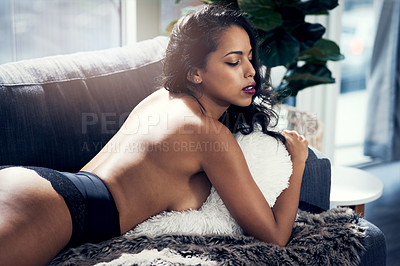 Buy stock photo Shot of a beautiful young woman lying on the sofa in lingerie at home
