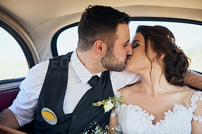 Buy stock photo Shot of a young couple kissing while travelling in a car on their wedding day