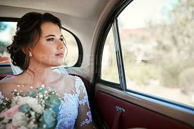 Buy stock photo Shot of a beautiful young bride travelling in a car on her wedding day
