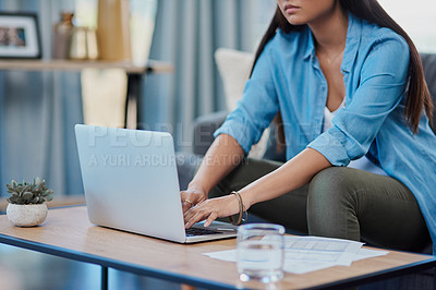 Buy stock photo Shot of an unrecognizable businesswoman using a laptop while working from home during the day