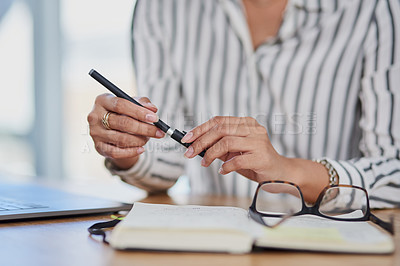Buy stock photo Shot of an unrecognizable businesswoman writing notes in her journal while working inside her office