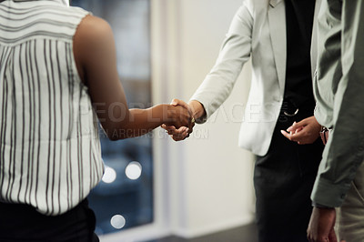 Buy stock photo Cropped shot of two unrecognizable businesswomen shaking hands inside a modern office