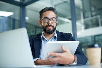 Buy stock photo Shot of a mature businessman using a digital tablet and laptop in an office