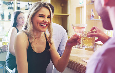 Buy stock photo Shot of a young man and woman toasting with their drinks in a nightclub