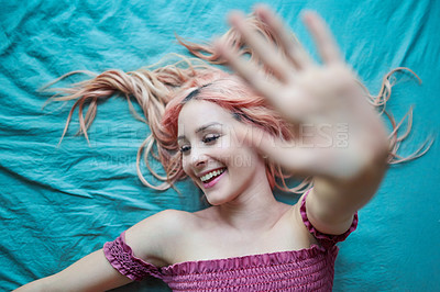 Buy stock photo Shot of a beautiful young woman with pink hair lying on a bed