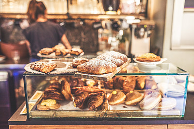 Buy stock photo Shot of a wide variety of baked goods inside of a display case ready to be ordered by customers inside of a coffee shop
